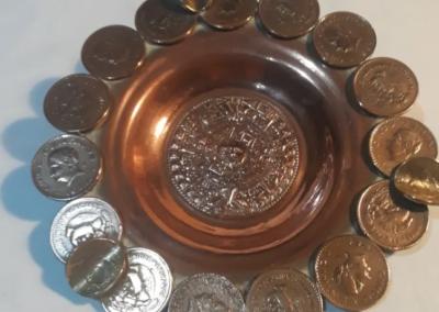 con monedas mexicanas y calendario maya
